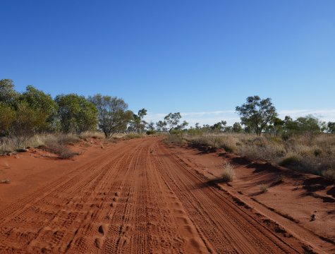 A dusty, red-dirt track under a blue sky.